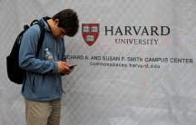 man in front of Harvard University sign looks at phone
