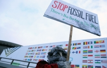 """A man wearing googles holds up a sign that says """"stop fossil fuel! there is no border in the sky!"""""""