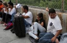 Men and women sit along a bridge