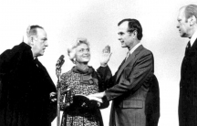 George H. W. Bush is shown with his hand on the bible nad right hand raised being sworn in as director of CIA.
