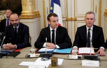 French President Emmanuel Macron, French Prime Minister Edouard Philippe, left,and French Ecology Minister Francois de Rugy dressed in suits and sitting behind a table