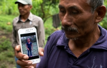 A man holds a phone with a picture of his granddaughter.