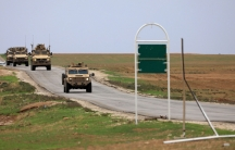 US troops driving armored vehicles are show driving on a road patroling near the Turkish border in Hasakah, Syria, 2018.