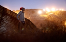 A migrant from Honduras stands in front of the border wall with the sun shining behind him