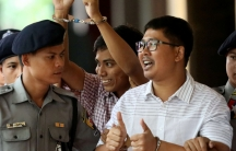 Two detained journalists in handcuffs give two thumbs up and fists raised.