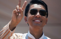 A man with glistening black hair wearing sunglasses waves to the crowd.