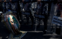 A migrant is shown wrapped with a banner depicting the Virgin of Guadalupe in front of a riot police with shield in Tijuana, Mexico.