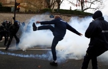 An ambulance driver in France is shown kicking a can of smoke with French riot police in the background.