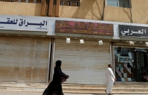 Saudi woman dressed in black robe walks behind a man wearing all white.