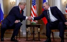 Trump and Putin shake hands.