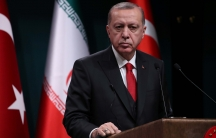 A middle-aged man stands at a podium with the Turkish and Iranian flag behind him.
