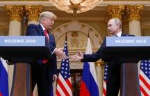 Donald Trump and Vladimir Putin shake hands behind two podiums reading Helsinki 2018