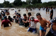 People link arms in a human chain and pull each other across a river
