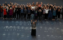Cuban artist Tania Bruguera stands with her arms in the air, and dozens of people behind her, standing in the same position