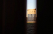 A slatted metal prototypes of a border wall is shown, photographed through the border wall in Tijuana, Mexico.