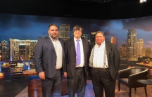 three men in suits stand on the set of a television show