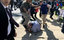 two men kick a protester on the ground