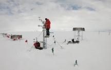 Researchers Scott Landolt and Mark Seefeldt set up an automatic snowfall measuring system in Antarctica.