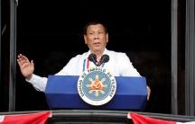 Philippine's President Rodrigo Duterte speaks behind a blue podium in a white shirt