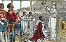 A king in a red robe kneels on one knee as a bishop places a crown on his head
