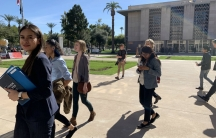 A group of young people walk in front of the Arizona state Capitol.