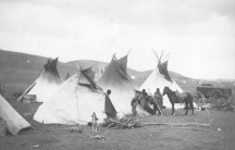 Black and white image of several people and a horse standing in front of teepees. A dog howls in the mid-foreground.