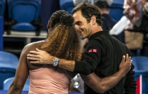 Tennis players Serena Williams and Roger Federer are shown embracing as they walk off the court together.