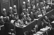 Defendents sit in a juror box and at tables during the Nuremberg trials in this historic photo