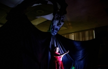 A young girl is lit up on a stage with an enormous dark monster behind her.