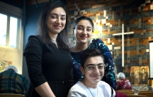 Three siblings smile and pose while sitting in the pew of a church