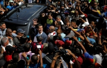 Venezuelan opposition leader Juan Guaido is shown surrounded about people on all sides next to a van.
