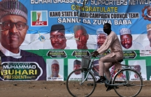 A cyclist drives pasts a campaign poster for President Muhammadu Buhari in a street