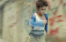 A boy in a blur running.