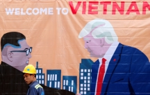A man is shown wearing a construction hard hat walking past a banner illustration depicting North Korean leader Kim Jong-un and US President Donald Trump