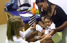 Germana Soares is shown holding her child next to a doctor holding a black and white striped card.