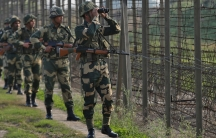 Six of India's Border Security Force soldiers are shown talking along the fenced border in a line.