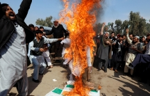 People chant slogans as they burn an effigy