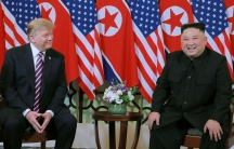 North Korea's leader Kim Jong-un and US President Donald Trump are shown sitting next two each other with US and North Korean flags behind them.