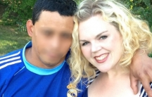 A closeup photo of a blonde woman wearing a blue shirt beside her husband, whose face has been blurred for privacy.