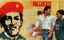 Venezuelans walk past a wall painted with the face of then presidential candidate Hugo Chávez. The leftist military leader tapped into a wave of discontent in the country with falling living standards and corrupt public institutions, December 1998.