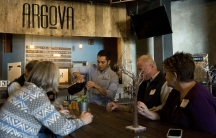 A man pours beer into a glass from a growler as several people are seated around a table.