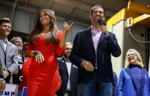 Woman stands in red dress next to politician.