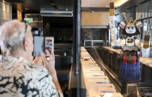 A man, left, takes a photo of a colorful robot that is also working as waitstaff in a restaurant.