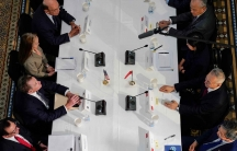An overhead view of people sitting at a table. In front of each person is a microphone and a name badge.