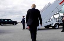 US President Donald Trump walks toward steps leading to an airplane
