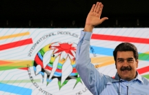 Maduro waves in front of a white flag