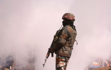 An Indian soldier stands guard while carrying a riffle with a lot of white smoke billowing behind him.