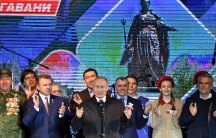 Russian President Vladimir Putin stands on a stage surrounded by others