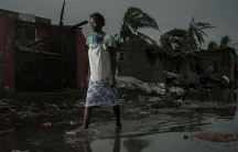 A woman is shown in ankle deep water walks down a flooded road with heavily damaged buildings in the background.