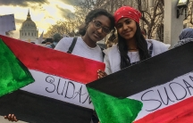 Two young women hold Sudanese flag posters.